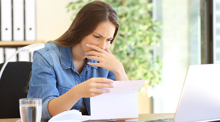 68984503 - worried entrepreneur girl working at office reading bad news in a letter on a desktop